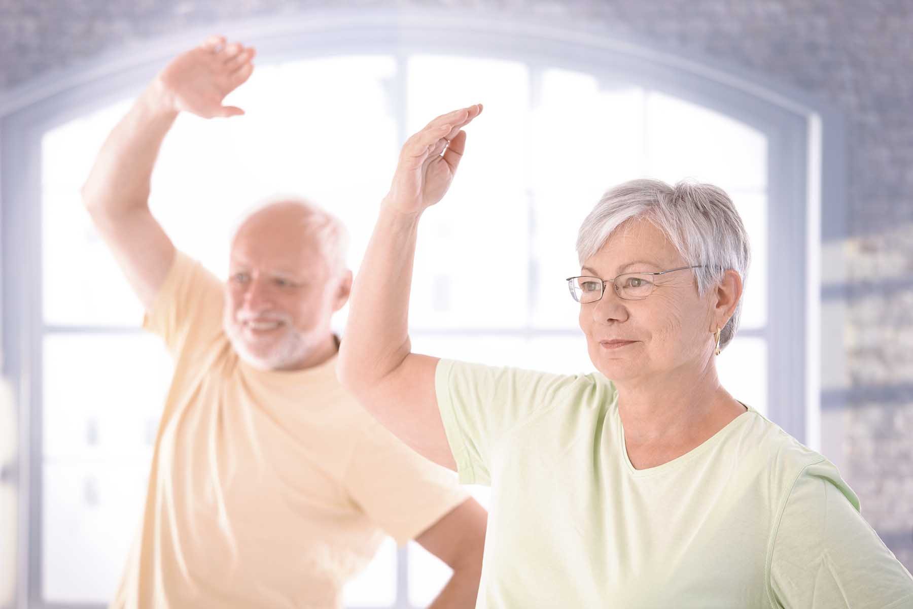 A photo of an older couple doing exercises.