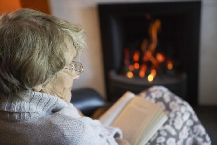 senior reading next to fireplace