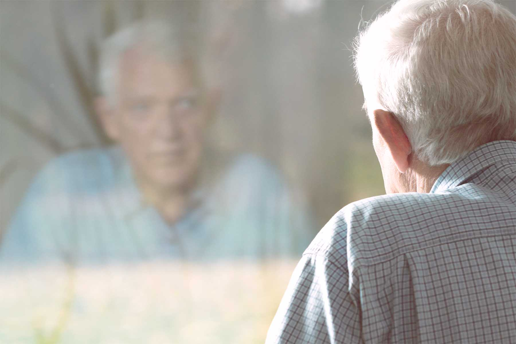 A photo of scared-looking senior man, looking at his reflection in a window.