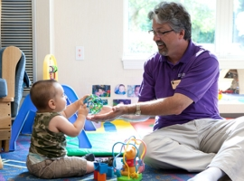 an educator playing with a baby
