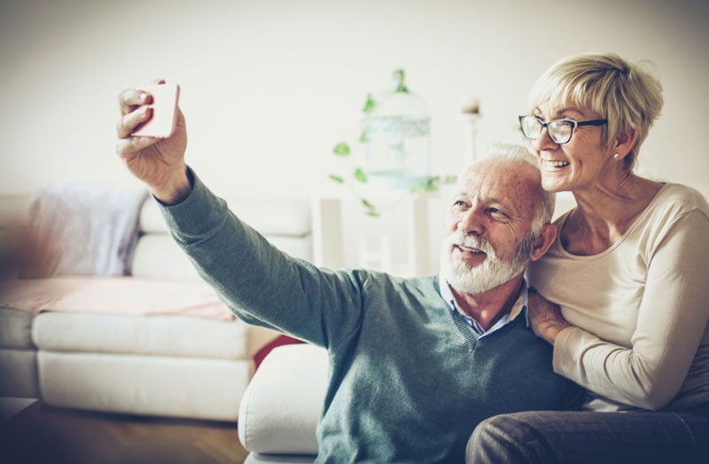 Senior couple taking self portrait together at home.